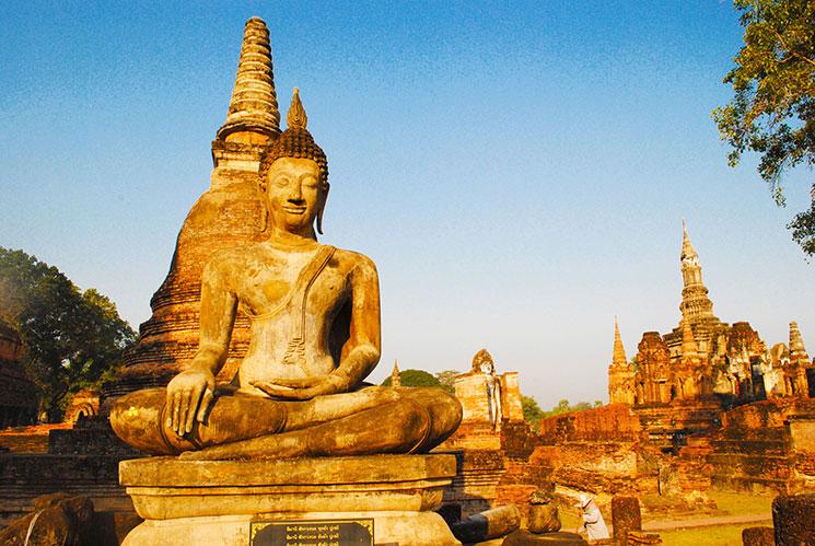 夕暮れ時のワット・マハタートの仏像。向かって右手に見えるのは寺院中央の仏塔
