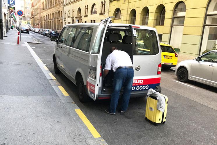 ブダペストの空港送迎シャトル「miniBUD」の車体。シルバーのボディに赤と紺のラインが目印です。