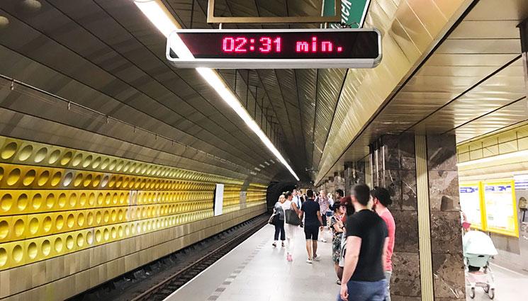 駅で電車を待つ人々と時計版
