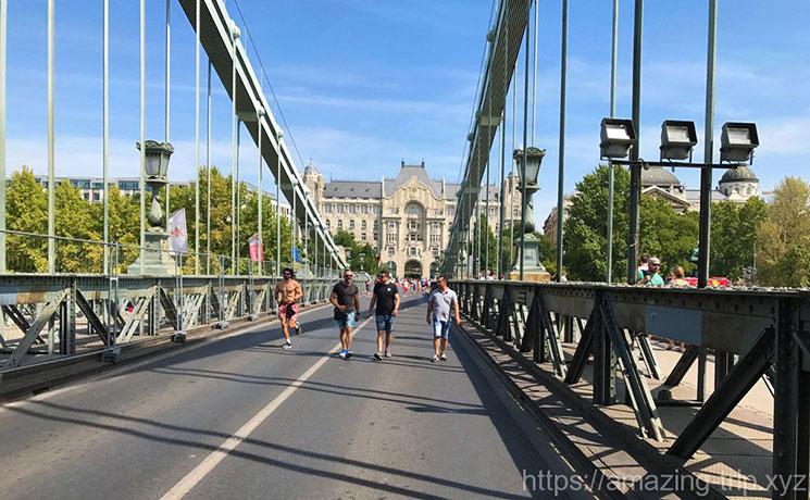 くさり橋の車道を歩く人々