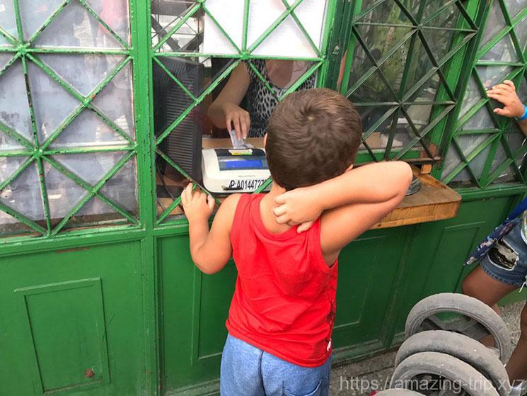ケーブルカーのチケット売り場でチケットを購入する子供