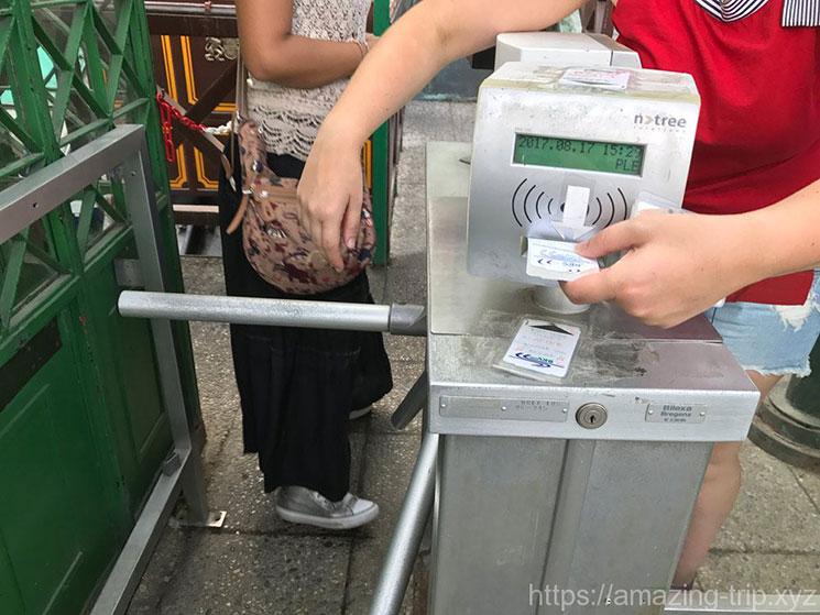 ケーブルカーの改札にチケットを挿入する旅行者