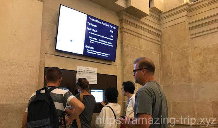 オペラ・ガルニエ館内設置の自動券売機でチケットを購入する人々