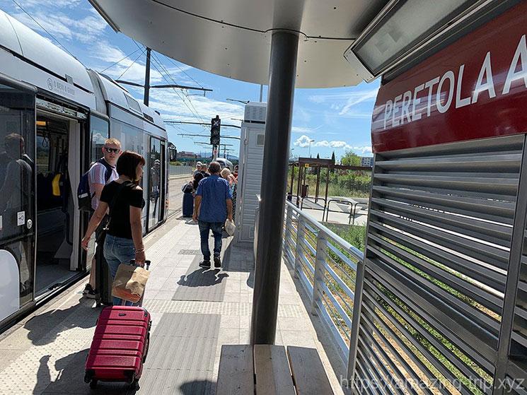 ペレトラ空港のトラム停留所とトラムを降りる乗客