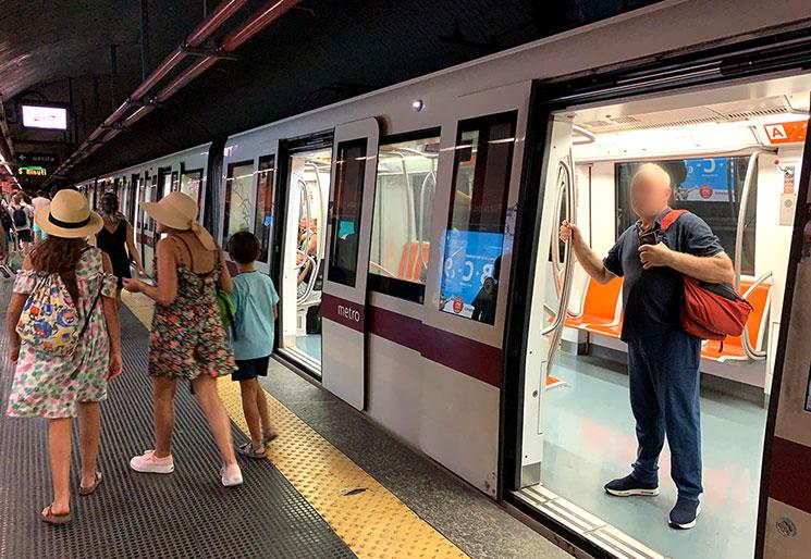 乗車ホームに到着した地下鉄から降車する人たち